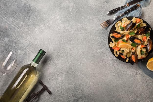 Pasta con frutti di mare e vino bianco sul tavolo di pietra. cozze e gamberi vista dall'alto.