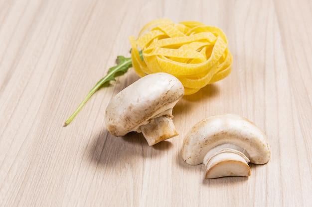 Pasta con funghi e rucola sulla tavola di legno nel ristorante. ingredienti sul dorso in legno
