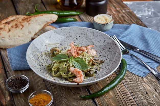 Pasta con gamberi e salsa al basilico. cucina italiana. pasta italiana tradizionale con gamberi e basilico, olio d'oliva e salsa al pesto.