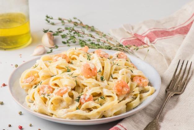 Pasta con gamberi, salsa cremosa, parmigiano e timo su un piatto. fettuccine mediterranee ai frutti di mare