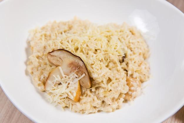 Pasta con i funghi in zolla bianca sulla tavola di legno leggera in un ristorante
