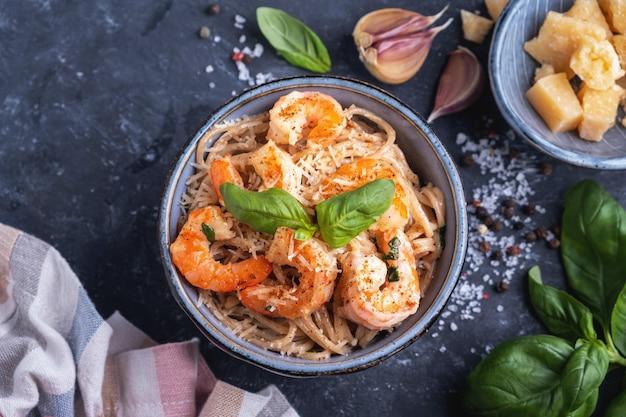 Pasta con i gamberi in una zolla, primo piano, vista superiore. pasta che cucina concetto, gli ingredienti e le spezie su una tavola con un piatto.