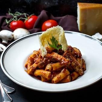 Pasta con pollo in salsa di pomodoro e formaggio grattugiato