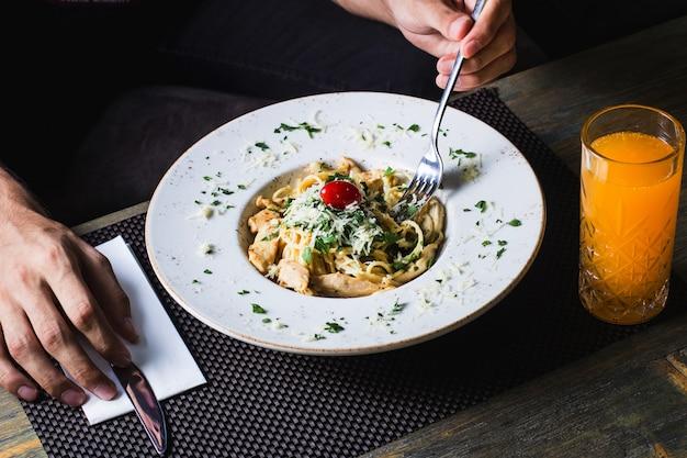 Pasta con pollo pomodori verdi e formaggio grattugiato servito con succo