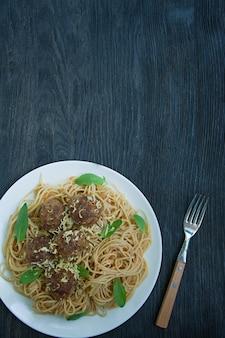 Pasta con polpette e prezzemolo in salsa di pomodoro