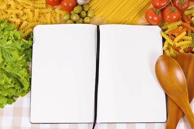 Pasta con ricettario bianco e tagliere