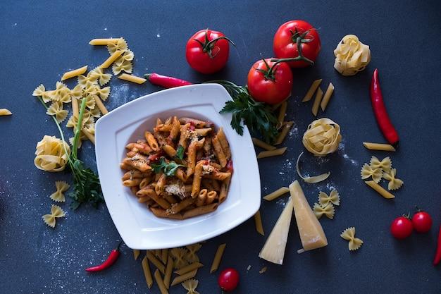 Pasta con salsa di pomodoro, aglio, peperoncino, parmigiano sul piatto bianco