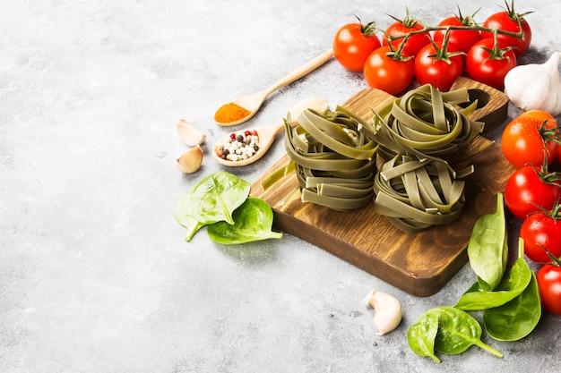Pasta cruda di tagliatelle con spinaci e ingredienti per cucinare