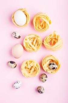 Pasta cruda tagliatelle crudo con uova di quaglia su un pastello rosa. vista dall'alto.