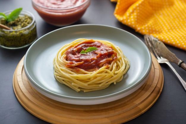 Pasta degli spaghetti con salsa al pomodoro e basilico in piatto su buio. piatto di pasta isolato.