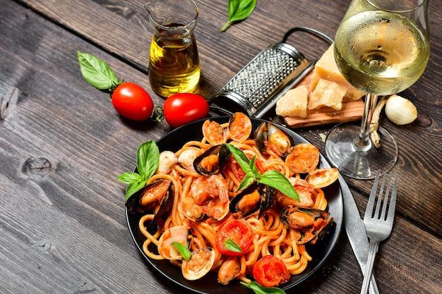 Pasta dei frutti di mare degli spaghetti con le vongole e i gamberetti con le cozze ed i pomodori in un piatto bianco con su una tavola di legno. ricetta della cucina italiana. vista dall'alto