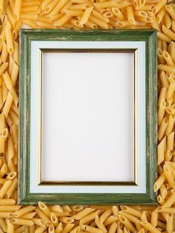 Pasta del penne di vista superiore con lo spazio della copia su fondo di legno