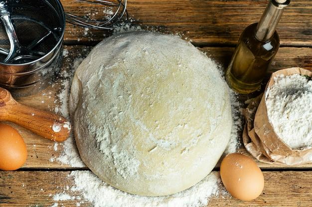 Pasta della pizza che cucina nella cucina domestica. pasta fatta in casa per pane, pizza, dolci e panini. ingredienti pasta su uno sfondo di legno rustico
