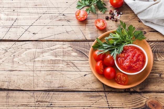 Pasta della salsa al pomodoro in una ciotola e pomodori freschi con prezzemolo su una tavola di legno copi lo spazio