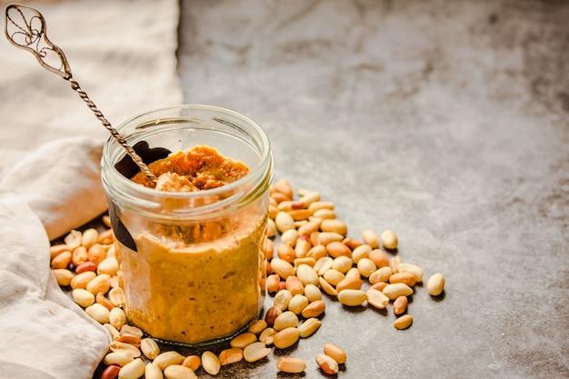 Pasta di arachidi in un barattolo aperto ed e cucchiaio, arachidi sul tavolo grigio.