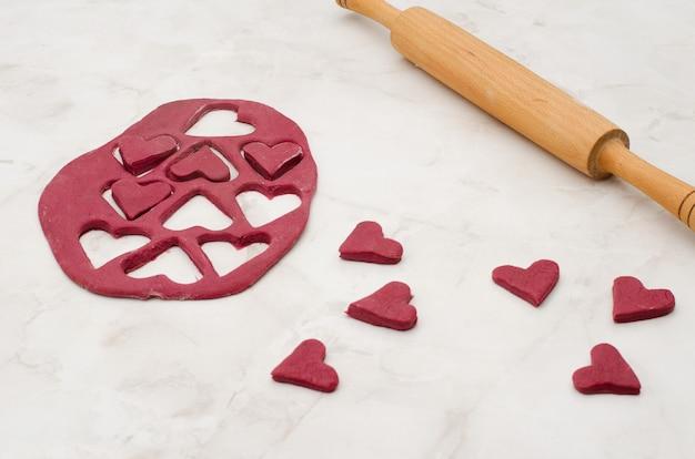 Pasta di barbabietola rossa con un mattarello e cuori tagliati su un tavolo bianco