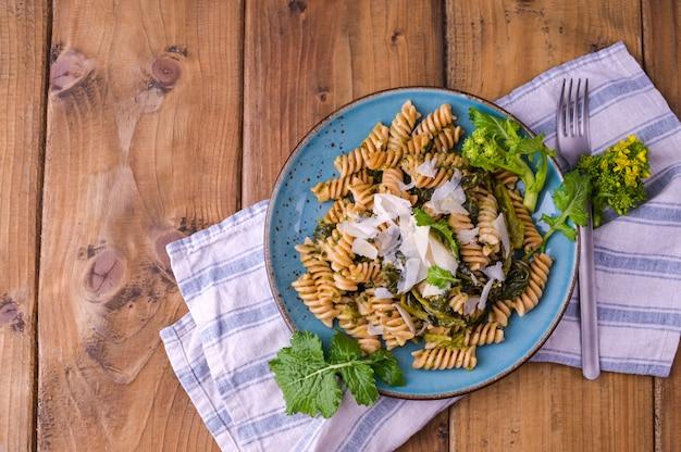 Pasta di cime di rapa in un piatto sopra con parmigiano su una tavola di legno. cibo tradizionale del sud italia, pugliese. foto in stile rustico. copia spazio