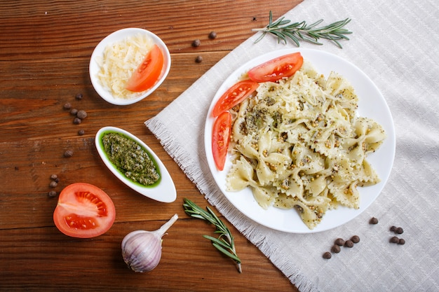 Pasta di farfalle al pesto, pomodori e formaggio su una tovaglia di lino su legno marrone