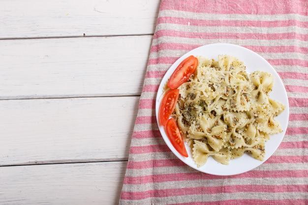 Pasta di farfalle con i pomodori ed il formaggio della salsa di pesto su una tovaglia di tela su fondo di legno bianco