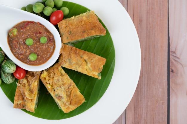 Pasta di gamberetti, insieme a frittata, cha-om e melanzane, disposte in un piatto bianco su un pavimento di legno.