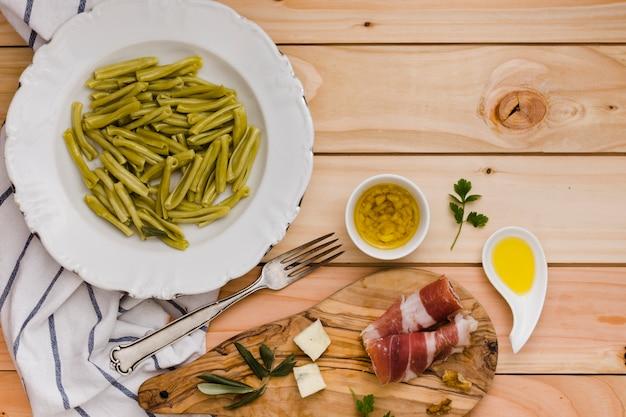 Pasta di gemelli agli spinaci; formaggio; pancetta e olio infuso sul tavolo di legno