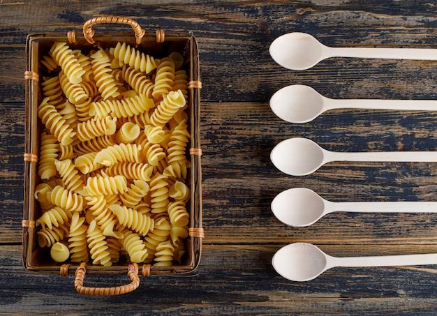 Pasta di maccheroni in un vassoio con la vista superiore dei cucchiai su fondo di legno