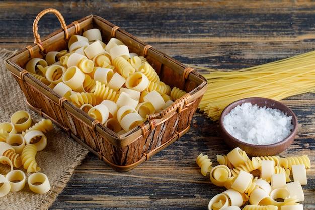 Pasta di maccheroni in un vassoio con sale, vista dell'angolo alto degli spaghetti su un fondo di legno