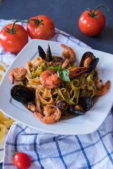 Pasta di mare con cozze e gamberetti sul piatto bianco. spaghetti su sfondo blu