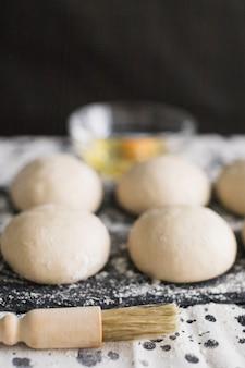 Pasta di pane cruda con pennello su sfondo nero