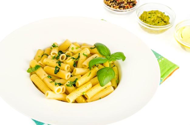 Pasta di penne con salsa di pesto di basilico di spinaci su piatto bianco.