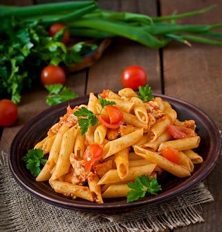 Pasta di penne in salsa di pomodoro con pollo e pomodori su un tavolo di legno