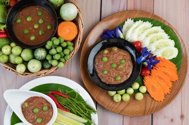 Pasta di peperoncino in una ciotola con melanzane, carote, peperoncino, cetrioli in un cestino sul tavolo di legno