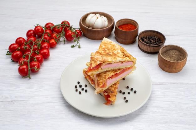 Pasta di pomodoro rosso vista frontale all'interno del piatto bianco con pomodori rossi freschi e aglio su bianco