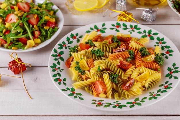 Pasta di rotini con insalata verde sulla tavola di natale