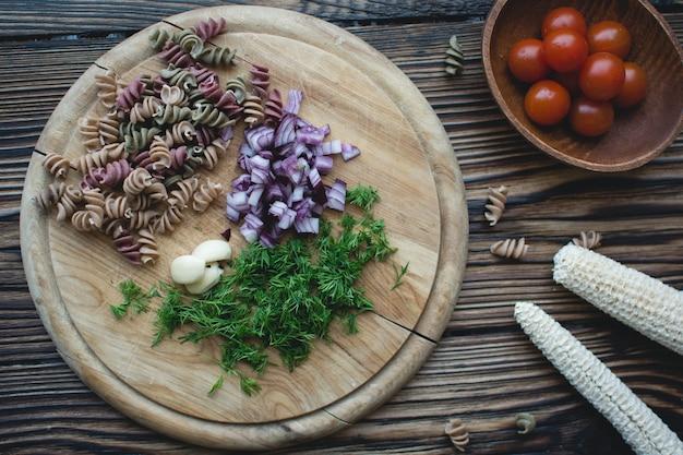 Pasta di rotini secchi colorati con aneto e cipolla