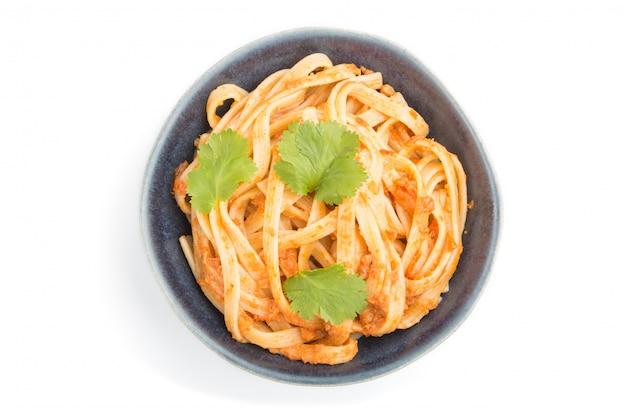 Pasta di semola con salsa di pesto di pomodoro, arancia ed erbe isolato su sfondo bianco. vista dall'alto, da vicino.