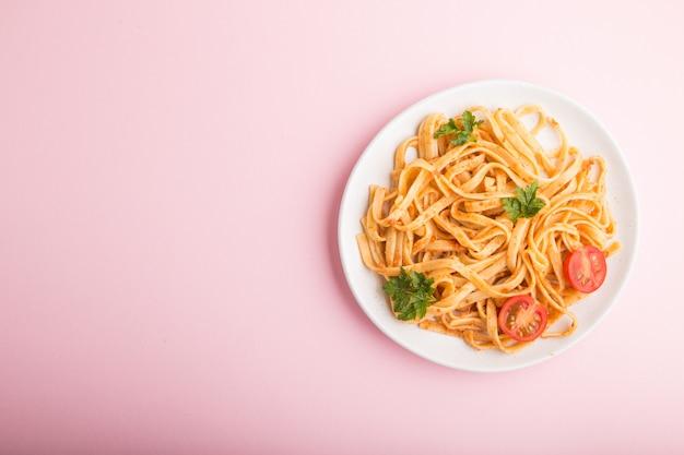 Pasta di semola con salsa di pesto di pomodoro, arancia ed erbe su uno sfondo rosa pastello. vista dall'alto, copia spazio.
