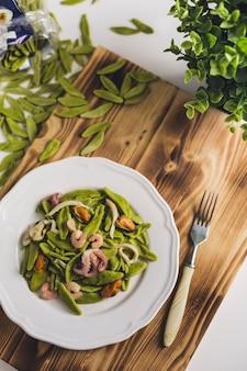 Pasta di spinaci con frutti di mare su un piatto bianco su una tavola di legno