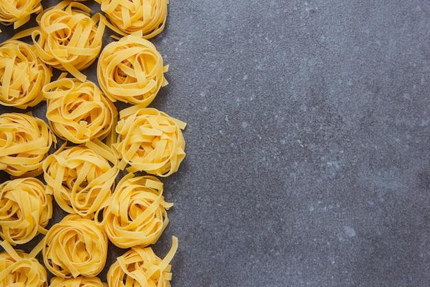Pasta di tagliatelle vista dall'alto su sfondo grigio. spazio orizzontale per il testo