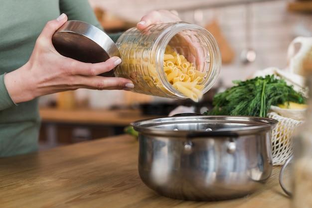 Pasta di versamento della donna del primo piano nella pentola di cottura