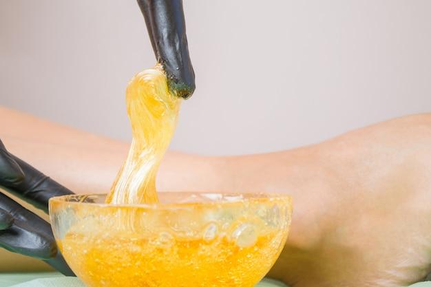 Pasta di zucchero o miele di cera per la rimozione dei capelli, gambe bella ragazza e mani in guanti neri