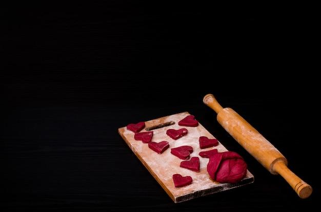 Pasta e biscotti a forma di cuore rossi crudi sul bordo di legno con farina, matterello di legno. tavolo nero