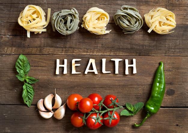 Pasta e verdure crude con salute del testo sulla vista superiore del fondo di legno