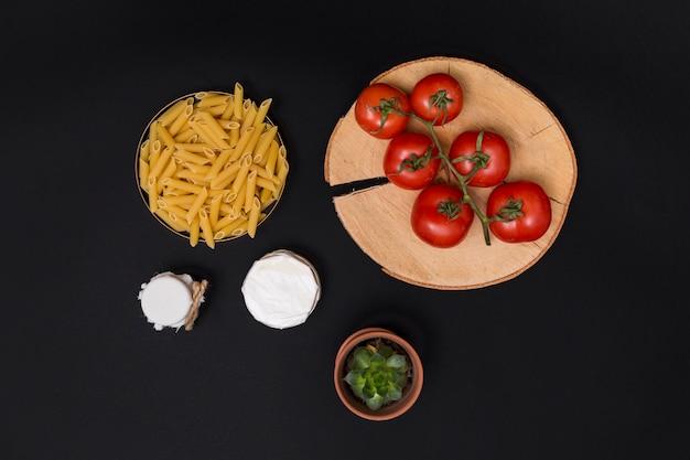 Pasta ed ingrediente crudi del penne con la pianta succulente su fondo nero