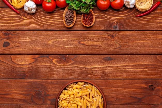Pasta ed ingredienti su fondo di legno con lo spazio della copia. vista dall'alto.