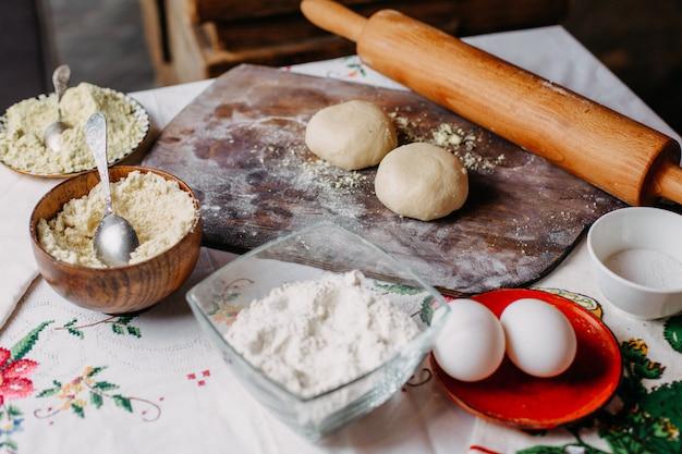 Pasta farina di pasta frolla in procinto di produrre pasta cuocere le uova di farina sulla scrivania rustica in legno marrone