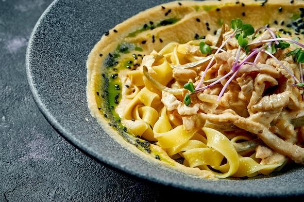 Pasta fatta in casa italiana con salsa bianca e tacchino o pollo in una ciotola grigia su sfondo nero