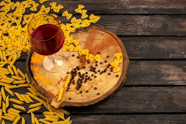 Pasta gialla cruda insieme a pepe e bottiglia di vino su uno scrittorio di legno rotondo su una tavola marrone