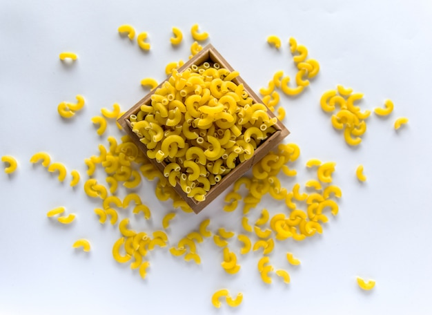 Pasta gialla cruda sul bachground bianco.