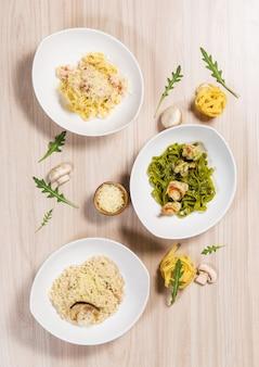 Pasta in piatti bianchi con diversi ingredienti sul tavolo in legno chiaro in un ristorante.